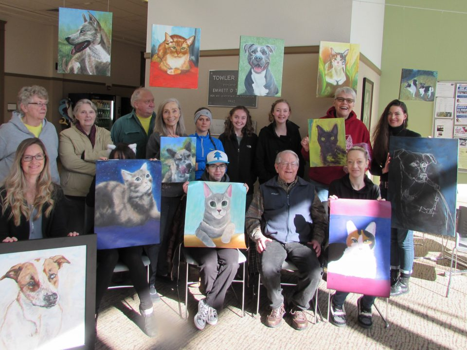 Students from CCC art class pose with paintings of animals from the local animal shelter