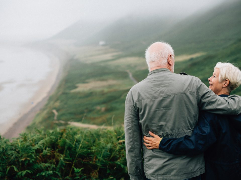 Senior couple at the pot of a hill overlooking a landscape