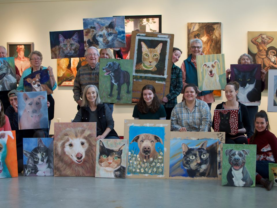 Students show off their paintings of local shelter cats and dogs that will be sold for a fundraiser for Clatsop Animal Assistance